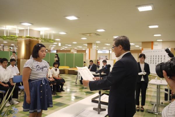 佐藤学長から表彰を受ける小学生