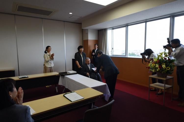 佐藤学長(右)に目録を贈呈する細井氏(中央)