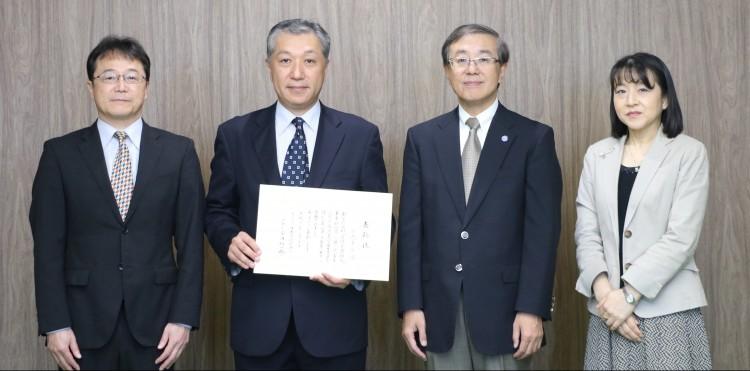 左から,伊藤教育推進機構長,表彰された小磯准教授,佐藤学長,郡理事