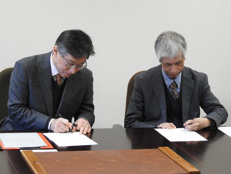 協定書に署名する名古屋大学佐久間研究科長(右)と今井学部長(左)