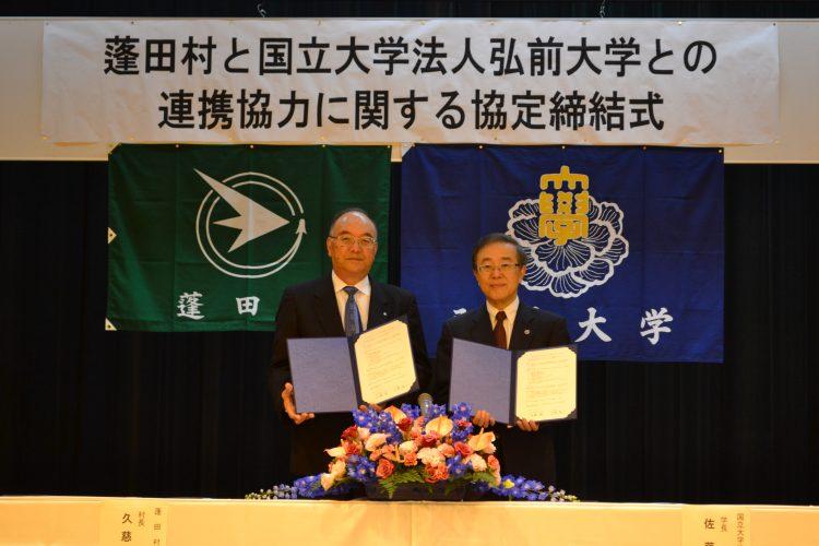 協定書を手にする久慈村長と佐藤学長