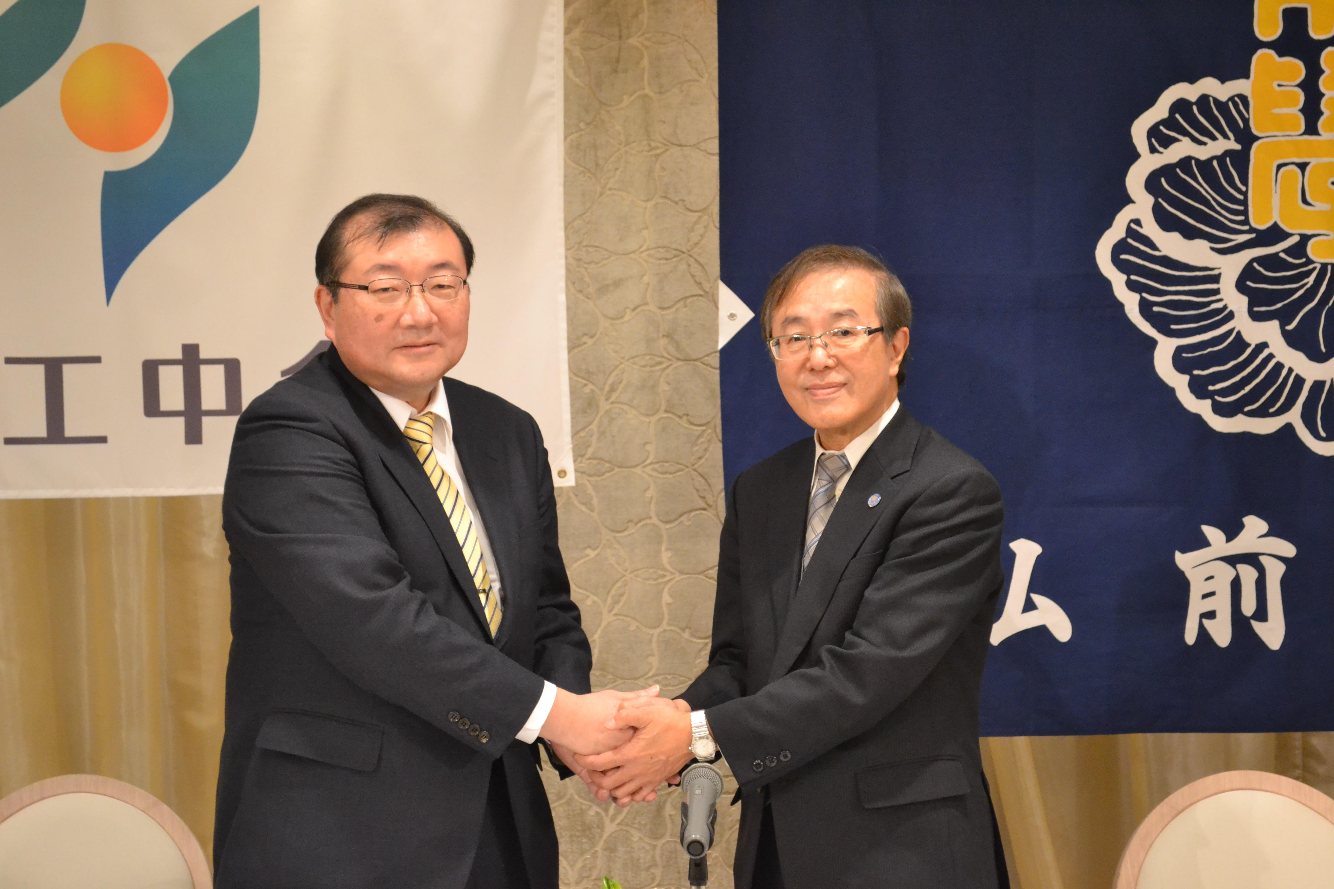 握手する河野取締役兼常務執行役員(左)と佐藤学長(右)